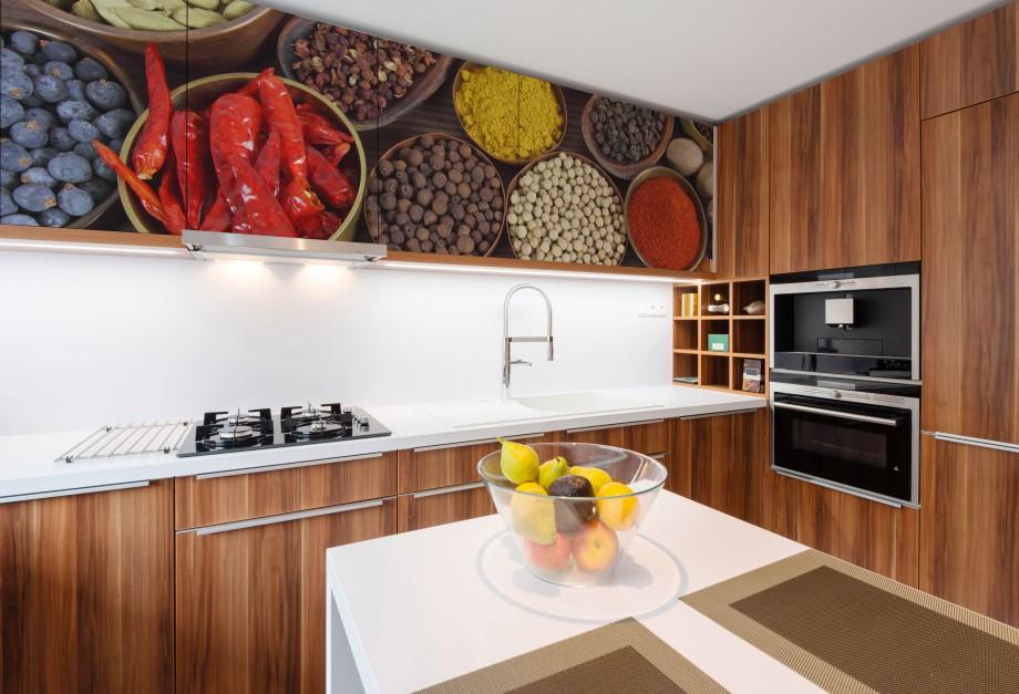Okleiny meblowe to prosty i oryginalny sposób na udekorowanie kuchennych mebli. Tutaj pokryto nimi rząd podwieszanych szafek. Motyw spożywczy, z kolorowymi przyprawami jest jak znalazł do kuchni. Pięknie komponuje się również z drewnianymi frontami. Fot. Dekornik.pl.