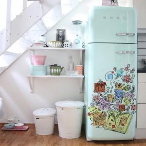 Jednym z najprostszych sposobów dekoracji kuchni są naklejki na sprzęt AGD. Błękitna lodówka udekorowana kolorową naklejką nadaje pomieszczeniu fikuśnego charakteru. Fot. Redro.