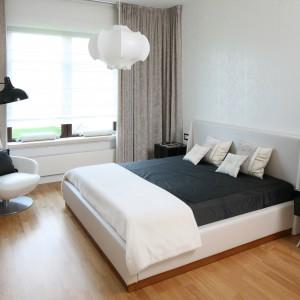 Czarna, stylizowana lampa zawieszona nad stolikiem nocnym z jednej strony łóżka to ciekawy pomysł na nowoczesną aranżację sypialni. Projekt: Katarzyna Koszałka. Fot.Bartosz Jarosz.