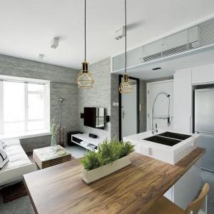 Nad blatem zawieszono dwie lampy, które formą nawiązują do stylistyki loftowej. Zamknięte w metalowe oprawki żarówki, komponują się z surowymi ścianami we wnętrzu. Z kolei ich pozłacana barwa, kolorystycznie pasuje do drewnianego stołu. Projekt: Millimeter Interior Design. Fot. Millimeter Interior Design.