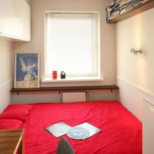 Czerwone akcenty: tkaniny, lampa wisząca ożywiają sypialnianą przestrzeń. Fot. Bartosz Jarosz.