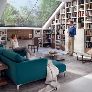 Niesymetryczny regał zagospodarowuje całą ścianę, pełniąc funkcję praktyczną i dekoracyjną zarazem. Aranżację ożywia modna sofa w butelkowym kolorze. Fot. Hulsta.