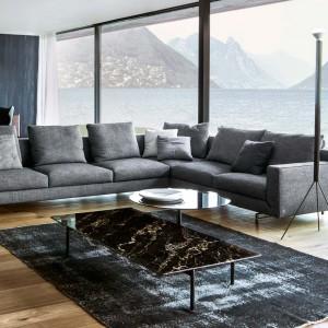 Główna zasada aranżacji nowoczesnego salonu zakłada, że im mniej - tym lepiej. W zupełności wystarczy więc szara sofa i stolik kawowy ze szklanym blatem. Fot. Busnelli.