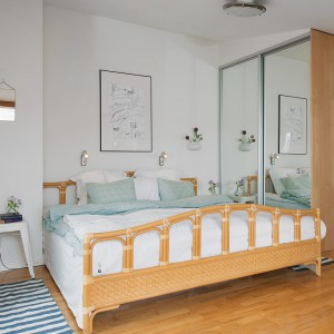 Wysoka szafa wykonana na wymiar z lustrzanymi frontami optycznie powiększa niewielką sypialnię i dostarcza wiele miejsca na przechowywanie. Fot. Alvem Makleri.
