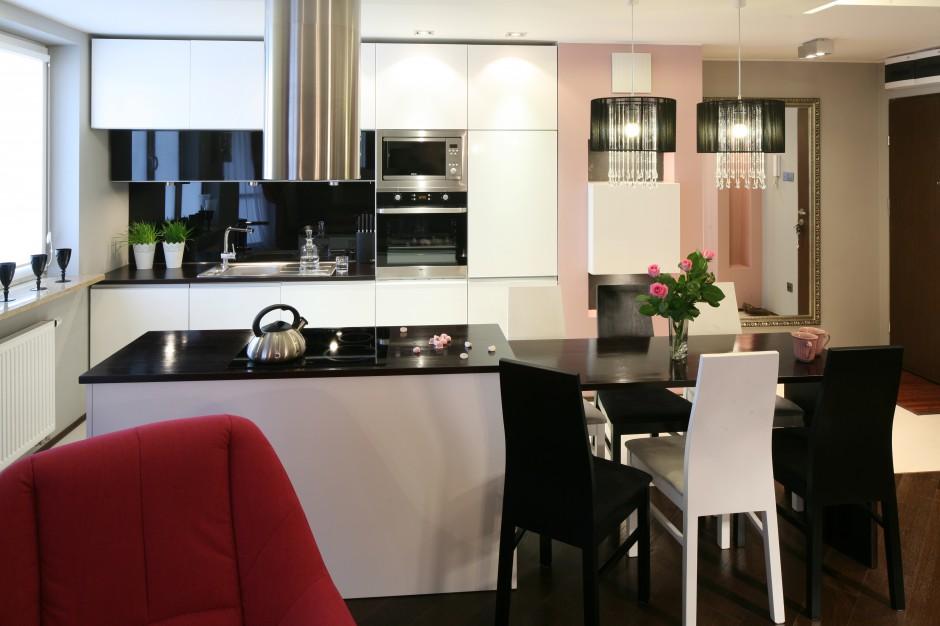Wyspę zlokalizowano wzdłuż umownej granicy salonu i kuchni. Przechodzi ona w niewielki stół jadalniany, poprowadzony wzdłuż tej samej granicy. Projekt: Marta Dąbrowska. Fot. Bartosz Jarosz.