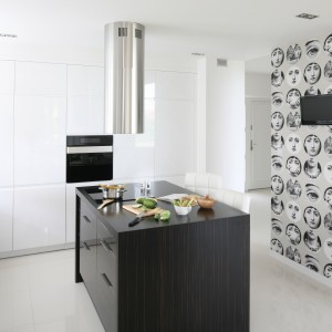Monochromatyczna aranżacja kuchni, w której wyspę umieszczono w samym centrum pomieszczenia. Ciemny kolor egzotycznego drewna kontrastuje z wysoką białą zabudową na połysk. Nad wyspą zawisł stalowy, nowoczesny okap. Projekt: Karolina i Artur Urban. Fot. Bartosz Jarosz.