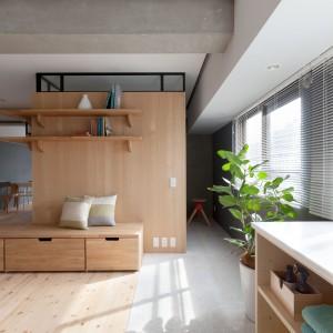 W części mieszkania, położonej po prawej stronie drewnianej ściany, urządzono strefę mycia. Zaakcentowano ją za pomocą innej posadzki na podłodze. Rozciąga się ona wzłuż ściany zewnętrznej mieszkania, od miejszej sypialni, po oddzielne pomieszczenie z wanną. Projekt: Chikara Ohno/Sinato. Fot. Toshiyuki Yano.