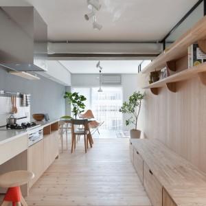 Jadalnię i aneks kuchenny umieszczono po tej samej stronie drewnianej ściany działowej. Stół jadalniany sąsiaduje bezpośrednio z panoramicznymi oknami i powierzchnią, przeznaczoną do relaksu. Projekt: Chikara Ohno/Sinato. Fot. Toshiyuki Yano.