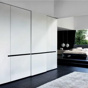 Biel pojemnej, przestronnej szafy Gliss 5TH została przełamana czarnym, poziomem dekorem. Fot. Molteni&C.