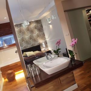 W połączonej z sypialnią łazience króluje naturalny styl oraz ciepłe drewno merbau, z którego wykonano parkiet w całej przestrzeni prywatnej. Projekt: Katarzyna Moraczewska. Fot. Tomasz Markowski.