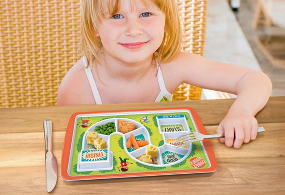 Prostokatny talerz przypominający planszę do gry. Do pokonania jest kilka przegródek z warzywami, a na końcu może czekać nagroda - słodka niespodzianka. Fot. The Gift Oasis.