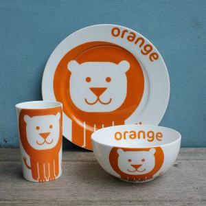 Kubek, miseczka i talerz - wszystkie naczynia zdobi uśmiechnięty pyszczek pomarańczowego lwa. Fot. China Gift Set.