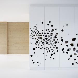 Otwory w białych panelach pełnią jednocześnie funkcję zintegrowanych z płytami uchwytów meblowych. Projekt: i29 interior architects. Fot. i29 interior architects.
