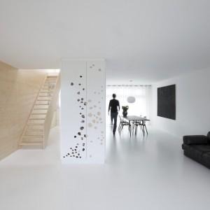 Ze skąpanym w bieli wnętrzem, efektownie kontrastują wyeksponowana na tle bieli duża kanapa oraz nowoczesny obraz w jadalni. Projekt: i29 interior architects. Fot. i29 interior architects.