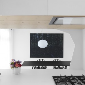 W obrębie powierzchni roboczej w kuchni, również postawiono na minimalizm. Okap zbudowany w zabudowę kuchenną, estetycznie się w niej chowa, a biały zlewozmywak podblatowy pozostaje niemal zupełnie niewidoczny, gdyby nie bardziej wyeksponowana bateria. Ciekawym rozwiązaniem jest tutaj czarna, tradycyjna płyta kuchenna, która wybija się na tle na wskroś nowoczesnej aranżacji. Projekt: i29 interior architects. Fot. i29 interior architects.