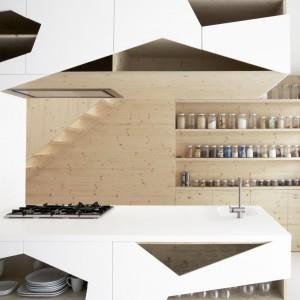 W obrębie półwyspu zlokalizowano powierzchnię gotowania i zmywania oraz praktyczny blat. Otwory wokół tej strefy są większe niż w zabudowanej części aneksu. Ścianę po drugiej stronie kuchni wykończono drewnem sosnowym i obudowano szafkami i praktycznymi półkami na przyprawy. Projekt: i29 interior architects. Fot. i29 interior architects.