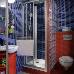 Kontrastowe kolory gwarantują magiczny charakter kąpieli. Wykorzystane do wzniesienie ścianki działowej pustaki szklane dodatkowo odbijają światło, które gra na ich powierzchni jak na tafli wody. Projekt: Marcin Konopka. Fot. Monika Filipiuk -Obałek.