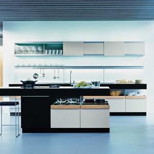 Bardzo efektowne rozwiązanie. Czarno-białą wyspę zestawiono z szafkami górnymi w szarym kolorze. Oryginalnym rozwiązaniem są przesuwne drzwiczki, pozbawione uchwytów oraz oświetlenie LED, podświetlające szklane półki. Fot. Poggenpohl, kuchnia +Modo.