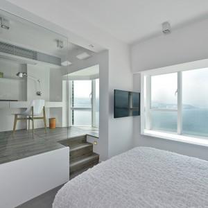 Z sypialni do gabinetu prowadzą niewielkie schody. Typową ściankę działową pomiędzy pomieszczeniami, zamieniono na estetyczne, delikatne przeszklenie. Biały kolor na ścianach, skomponowany, panoramiczne okna i częsciowo otwarte pomieszczenia, nadają wnętrzu lekkości i przestrzenności. Projekt: Millimeter Interior Design. Fot. Millimeter Interior Design.