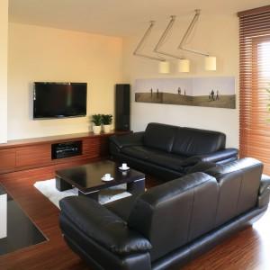 Nowoczesny, nieco minimalistyczny wystrój salonu ocieplają starannie dobrane naturalne materiały wykończeniowe oraz ich stonowana, beżowo-brązowa kolorystyka. Projekt: Ola Wołczyk. Fot. Bartosz Jarosz.