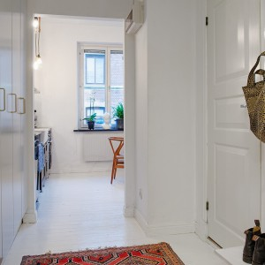 Świetnie zorganizowana przestrzeń przedpokoju. Na lewej ścianie zlokalizowano cztery pojemne szafy, chowające się w ścianie, za gładkimi frontami. Pomalowane na szaro powierzchnie drzwiczek, ozdobiono mosiężnymi uchwytami. Fot. Alvhem Makleri & Interior / Fredrik J Karlsson, SE360.