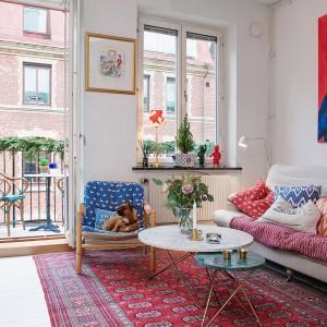Stos przytulnych dekoracyjnych poduch wprowadza do wnętrza domowy klimat. W salonie jest miło i przytulnie - co potwierdza również wypoczywający w fotelu pies. Fot. Alvhem Makleri & Interior / Fredrik J Karlsson, SE360.