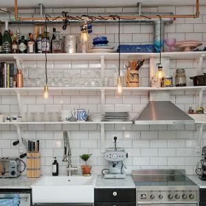 Klasyczne górne szafki nad blatem kuchennym zastąpiono otwartymi półkami. Wprowadzają one do wnętrza wrażenie przestronności i lekkości aranżacji. Fot. Alvhem Makleri & Interior / Fredrik J Karlsson, SE360.