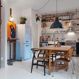 W kuchni i jadalni, industrialny styl miesza się z klasyczną stylistyką. Drewniany stół, stylizowane krzesła i tradycyjne kafle na ścianie nad blatem kuchennym w ciekawy sposób balansują z czarną, loftową lampą i żarówkami wiszącymi nad blatem. Fot. Alvhem Makleri & Interior / Fredrik J Karlsson, SE360.