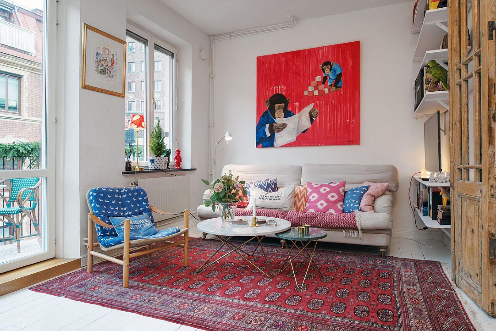Wiszący na ścianie obraz komponuje się kolorystycznie ze wzorzystym dywanem na podłodze w salonie. Pod kolor dobrano także poduszki na kanapie oraz akcesoria dekoracyjne na parapecie. Fot. Alvhem Makleri & Interior / Fredrik J Karlsson, SE360.