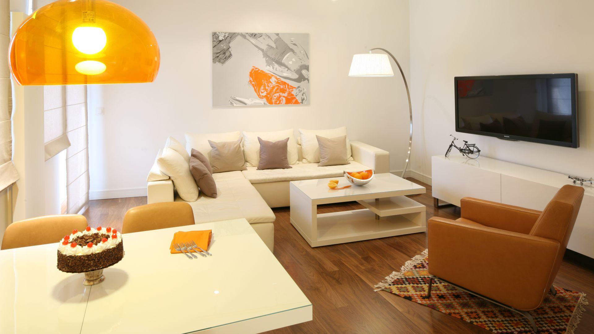 Dominujący w salonie jasny kolor ciekawie przełamują elementy w różnych odcieniach brązu oraz pomarańczowe dekoracje. Fot. Bartosz Jarosz.
