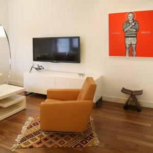 Ściany w całym mieszkaniu zdobią ekstrawaganckie obrazy w ciepłych, czasem krzykliwych kolorach, zakupione na aukcji młodej sztuki Dessa. Fot. Bartosz Jarosz.