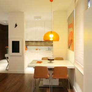 Ściana nad blatem kuchennym, imitująca drewno, koresponduje z parkietem oraz ciepłym kolorze krzeseł w jadalni. Fot. Bartosz Jarosz.