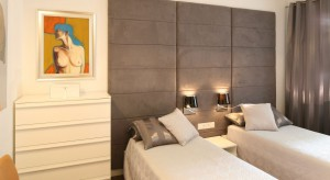 Tapicerowana ściana, przyjemne beże, proste formy mebli w połączeniu z wyszukanymi obrazami tworzą spójne, ale i oryginalnewnętrze. Ta sypialnia wprost zachęca do odpoczynku.