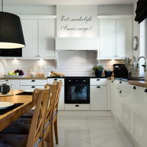 Romantyczna wariacja na temat kuchni skandynawskiej. Białe meble z prostym frezowaniem wykończono na połysk. Drewniany blat kuchenny w naturalnym, ciepłym kolorze komponuje się ze stołem jadalnianym i nadaje wnętrzu przytulności. Fot. Pracownia Mebli Vigo/Artur Krupa.