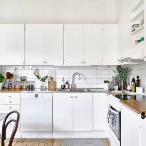 Kuchnię w mieszkaniu, wystawionym na sprzedaż przez szwedzką agencję Stadshem. Proste fronty mebli kuchennych zestawiono z drewnianym blatem kuchennym. Ściany pomalowano w całości na biało, a nad blatem pokryto białymi płytkami. Fot. Stadshem.