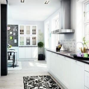 Ciemne drewno zestawione z uniwersalną bielą. Białe meble kuchenne zwieńczono ciemnobrązowym blatem, który kolorystycznie komponuje się z belką podtrzymującą strop. Fot. HTH.