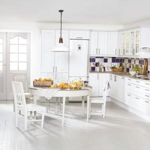 Romantyczna kuchnia, w której centrum jest biały, delikatnie stylizowany stół i towarzyszące mu białe krzesła. Meble kuchenne są delikatnie zdobione, z przeszkleniami ze szprosami w górnych szafkach. Białą kuchnię przełamano granatowymi płytkami nad blatem. Podłoga - obowiązkowo jasna! Fot. Marbodal.