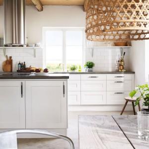 Piękna skandynawska kuchnia. Lekko frezowane białe fronty mebli kuchennych zestawiono z ciemnym, kontrastującym blatem. Klimat w kuchni budują również dodatki: ekspres do kawy w stylu retro, drewniany stołek z surowego drewna oraz pleciony abażur. Fot. Ballingslov.
