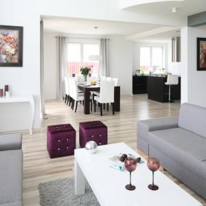 Pikowane, sześcienne siedziska w kolorze bakłażana są efektowną dekoracją szarego salonu. Projekt: Karolina i Artur Urban. Fot. Bartosz Jarosz.