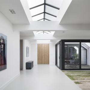 Pomiędzy master bedroom a przestrzenią dzienną wpasowano urokliwe patio. Komunikacja strefy dziennej z prywatną odbywa się zarówno przez wysokie, drewniane drzwi, jak i przez atrium. Projekt: i29 interior architects. Fot. Ewout Huibers.
