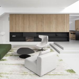 Zabudowa na ścianie w salonie kolorystycznie dopasowana została do zabudowy i mebli w kuchni i jadalni. Matowa czerń i naturalne, dębowe drewno są pięknie wyeksponowane na tle białych ścian. Projekt: i29 interior architects. Fot. Ewout Huibers.