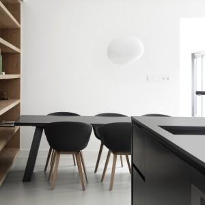 Fronty i blat wyspy kuchennej wykończono na czarny mat. Eleganckie powierzchnie komponują się kolorem i teksturą z siedzeniami krzeseł w jadalni i stołem jadalnianym. W czerni wybrano także baterię zlewozmywakową. Projekt: i29 interior architects. Fot. Ewout Huibers.