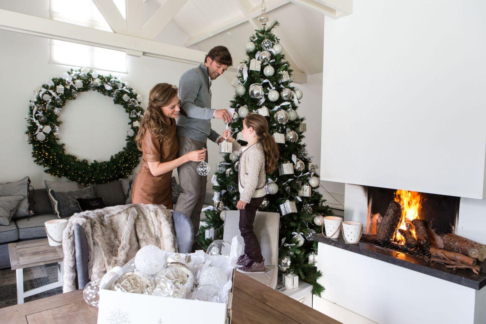 Jasne ozdoby na drzewko świąteczne to niezwykle stylowa propozycja. Biało-srebrne bombki pięknie harmonizują z zieloną choinką i ogromnym wieńcem. Takie ozdoby znakomicie sprawdzą się w nowoczesnych jasnych wnętrzach. Fot. House&More.