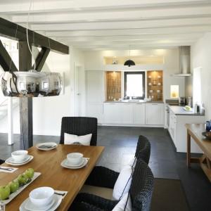 Otwarta kuchnia i jadalnia stanowią wspólną strefę przygotowywania i spożywania posiłków. Drewniany stół jadalniany pasuje kolorem i stylistyką do komody na ścianie, łączącej dwa pomieszczenia. Komponuje się także ze ścianą nad blatem. Projekt: Kamila Paszkiewicz. Fot. Bartosz Jarosz.