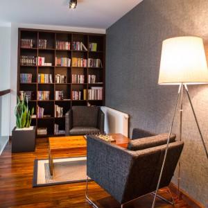 Na antresoli zlokalizowano elegancką, stylową bibliotekę. Na wysokości całej ściany poprowadzono praktyczne półki. Drugą ścianę pokryto stylową tapetą, komponującą się kolorystycznie z dwoma fotelami. Projekt: Pracownia Projektowania Wnętrz Viva Design, Fot. Tadeusz Poźniak.