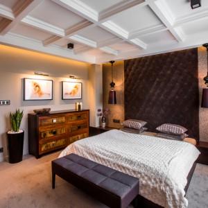 W pięknej sypialni małżeńskiej ustawiono duże podwójne łóżko, stylizowaną komodę i elegancki podnóżek. Zamiast tradycyjnych szafek nocnych, przy ścianie, na której zlokalizowano łóżko, poprowadzono na szerokość całego pomieszczenia, elegancką drewnianą szafkę. Wysoki, tapicerowany zagłówek, efektowne dekoracyjne lampy, zastępujące tradycyjne lampki nocne oraz postarzana komoda, wprowadzają do wnętrza element szyku. Projekt: Pracownia Projektowania Wnętrz Viva Design, Fot. Tadeusz Poźniak