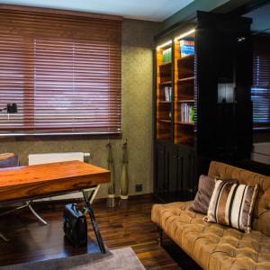 Na parterze zlokalizowano praktyczny gabinet, w którego aranżacji dominuje stylowe drewno palisander, z którego zrobiono biurko oraz którym wykończono podłogę. Żaluzje w oknach zapewniają spokój potrzebny do pracy. Wypoczynek w przerwach gwarantuje skórzana, pikowana sofa. Meble lakierowane na wysoki połysk z okleiną fornirowaną palisander santos. Projekt: Pracownia Projektowania Wnętrz Viva Design, Fot. Tadeusz Poźniak.