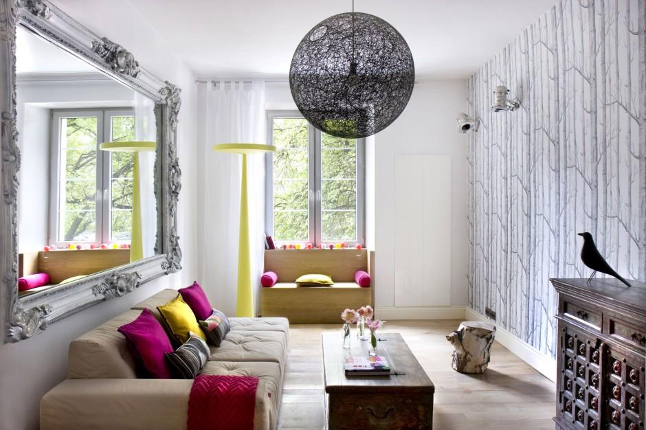 Piękny salon stanowi uosobienie całego wnętrza. Spotykają się tutaj nowoczesne rozwiązania z wieloletnimi zabytkowymi meblami. Nowoczesna, designerska lampa i żywiczna figurka kontrastują z lustrem w ozdobnej ramie. Pod oknem zlokalizowano niewielkie siedzisko - romantyczny akcent w eklektycznej przestrzeni. Projekt: Pracownia architektoniczna STUDIO.O. Fot. Katarzyna Sawicka.