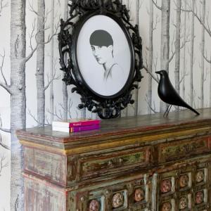 Piękna, drewniana komoda w salonie to zabytkowy mebel, z duszą. Z tak wyjątkowym elementem wyposażenia należało skomponować równie stylowe dodatki. Postawiono na elegancką, czarną, designerską figurkę w kształcie ptaka oraz stylizowaną czarną ramkę ze zdjęciem - również stylizowanym na starą fotografię. Projekt: Pracownia architektoniczna STUDIO.O. Fot. Katarzyna Sawicka.