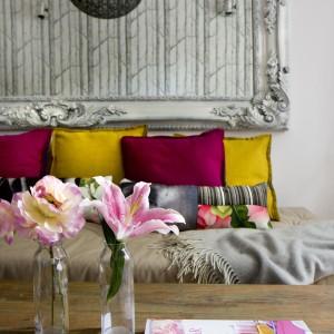 Kanapę w salonie ozdabiają dekoracyjne poduszki w żywych barwach intensywnego różu i jesiennej żółci. Efektownie kontrastują z szarą narzutą i ramą lustrzaną oraz tapetą na ścianie. Projekt: Pracownia architektoniczna STUDIO.O. Fot. Katarzyna Sawicka.